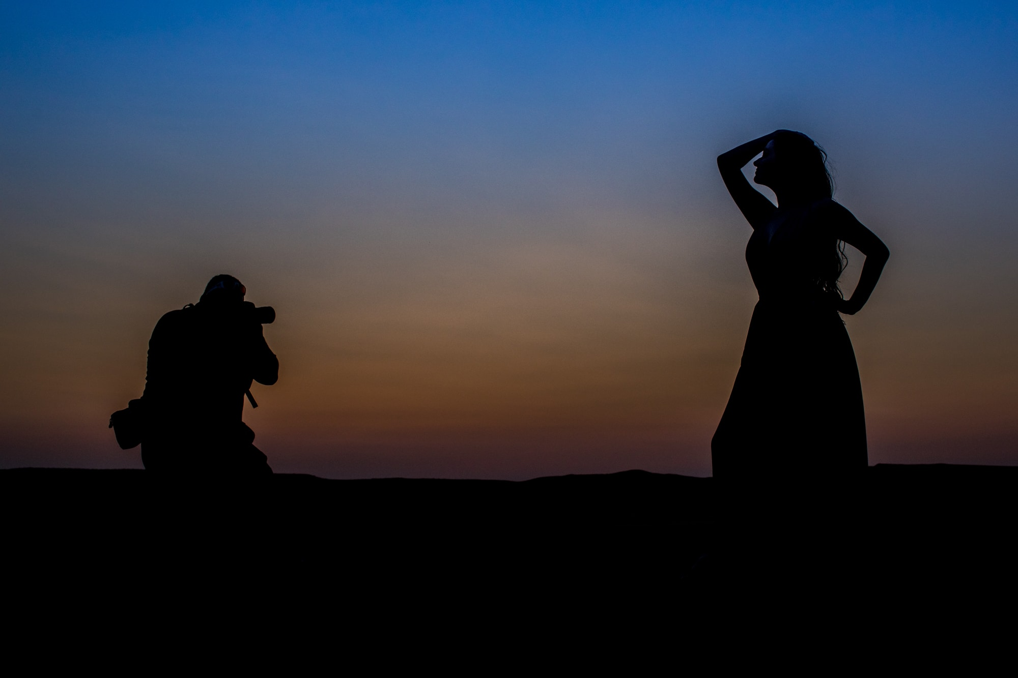photographer and model silhouetted against the sunset