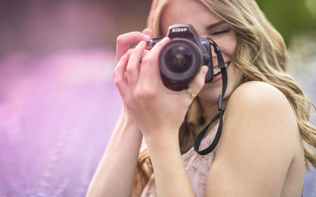 young woman smiling from behind a camera