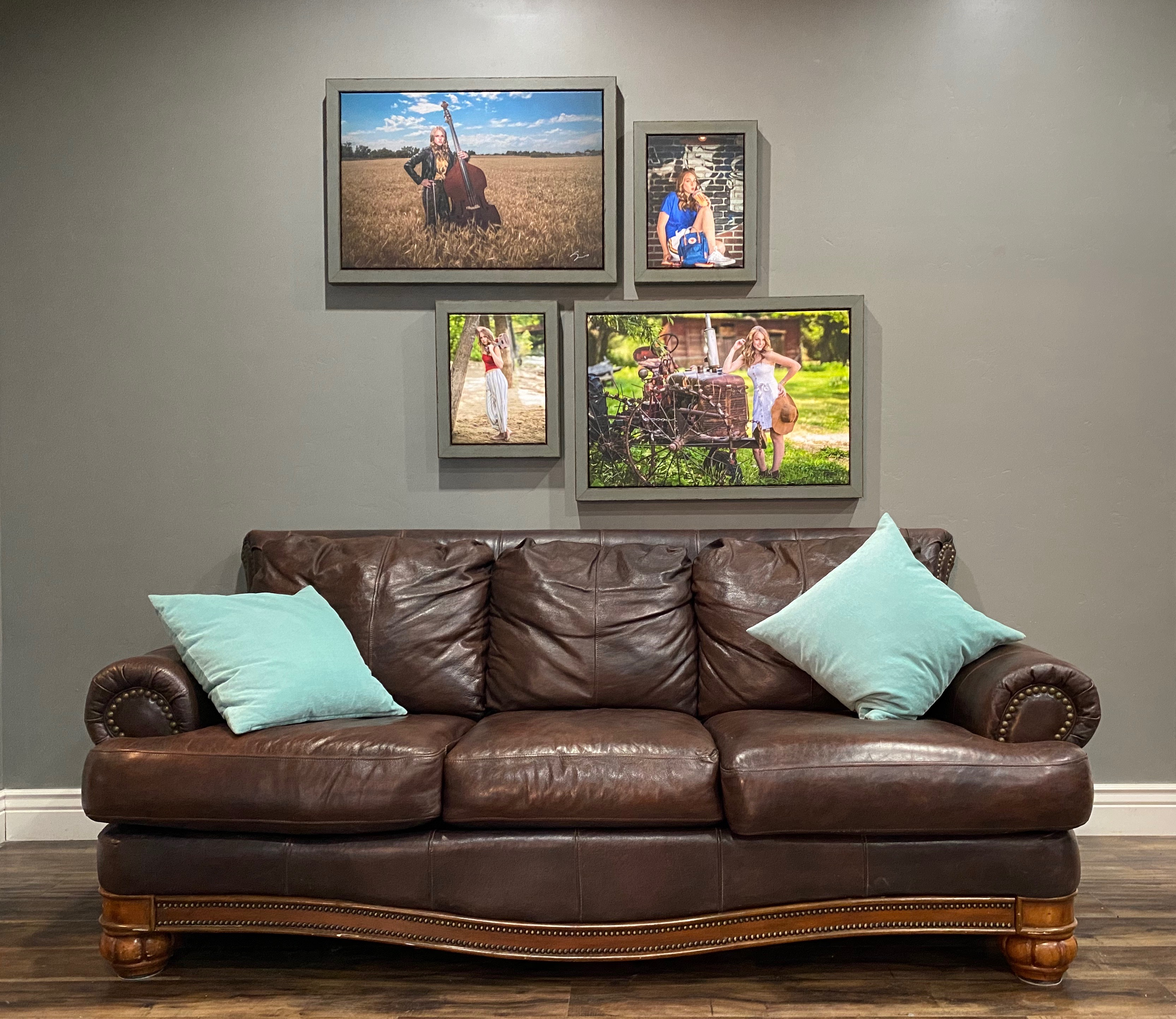 Framed senior portraits on a wall above a leather couch