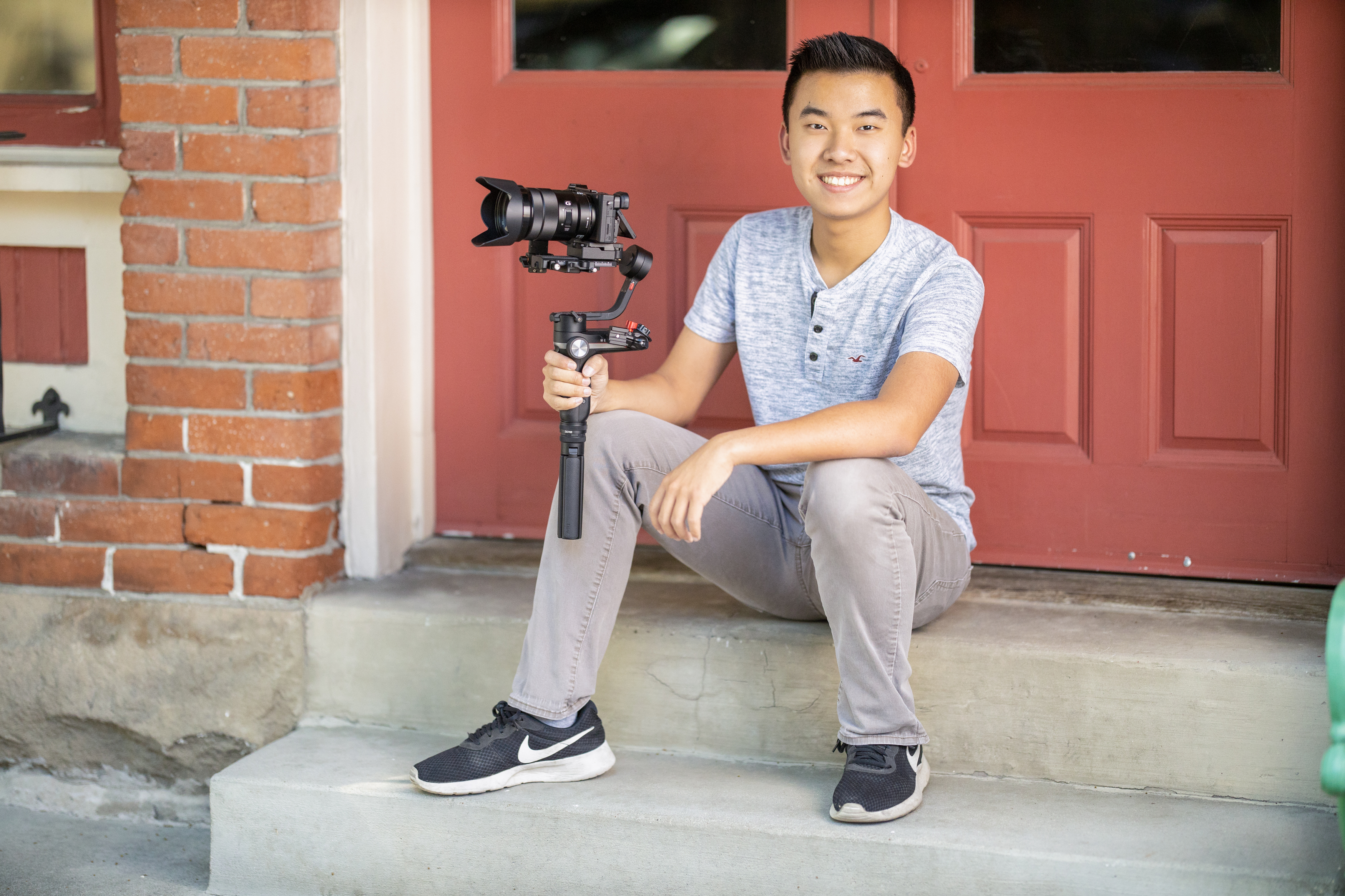Young man sitting on a porch with video equipment