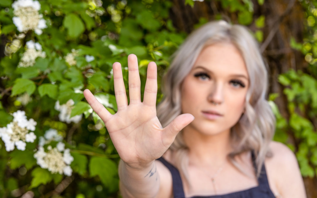 young woman holding up 5 fingers against a floral background