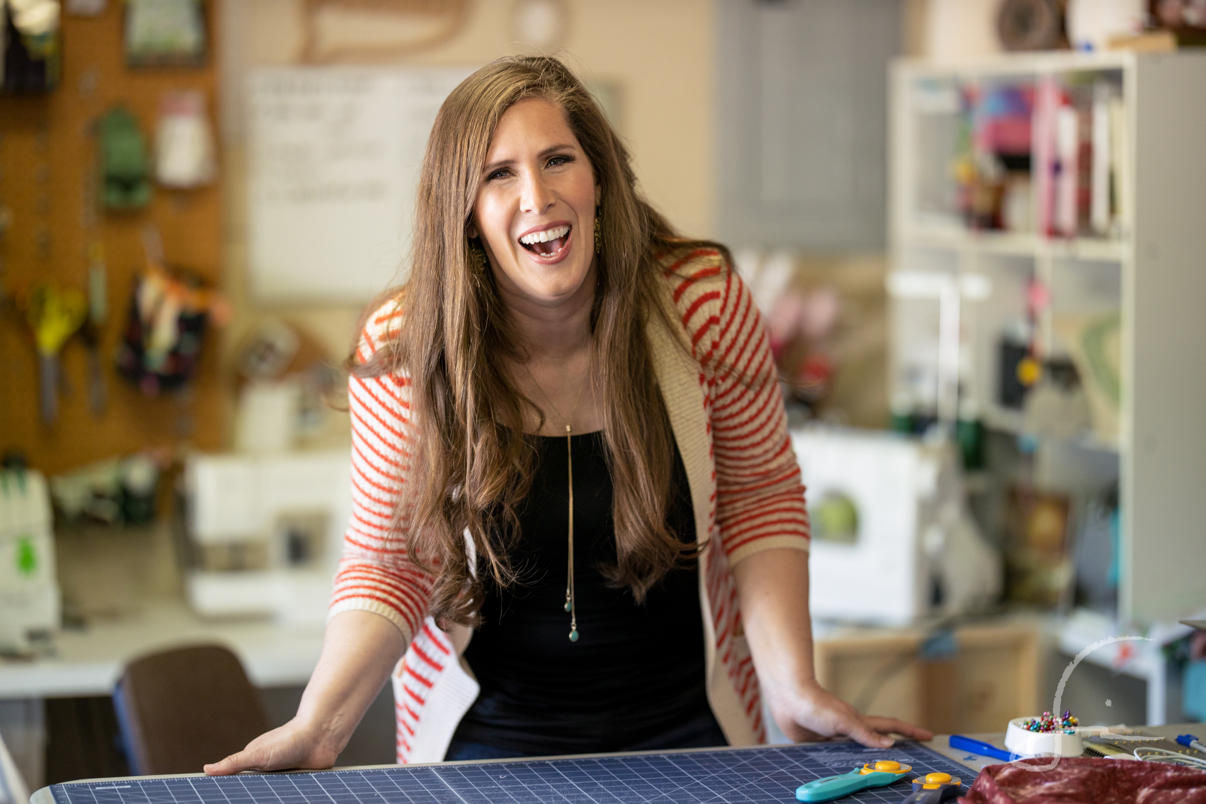 Woman in sewing studio laughing