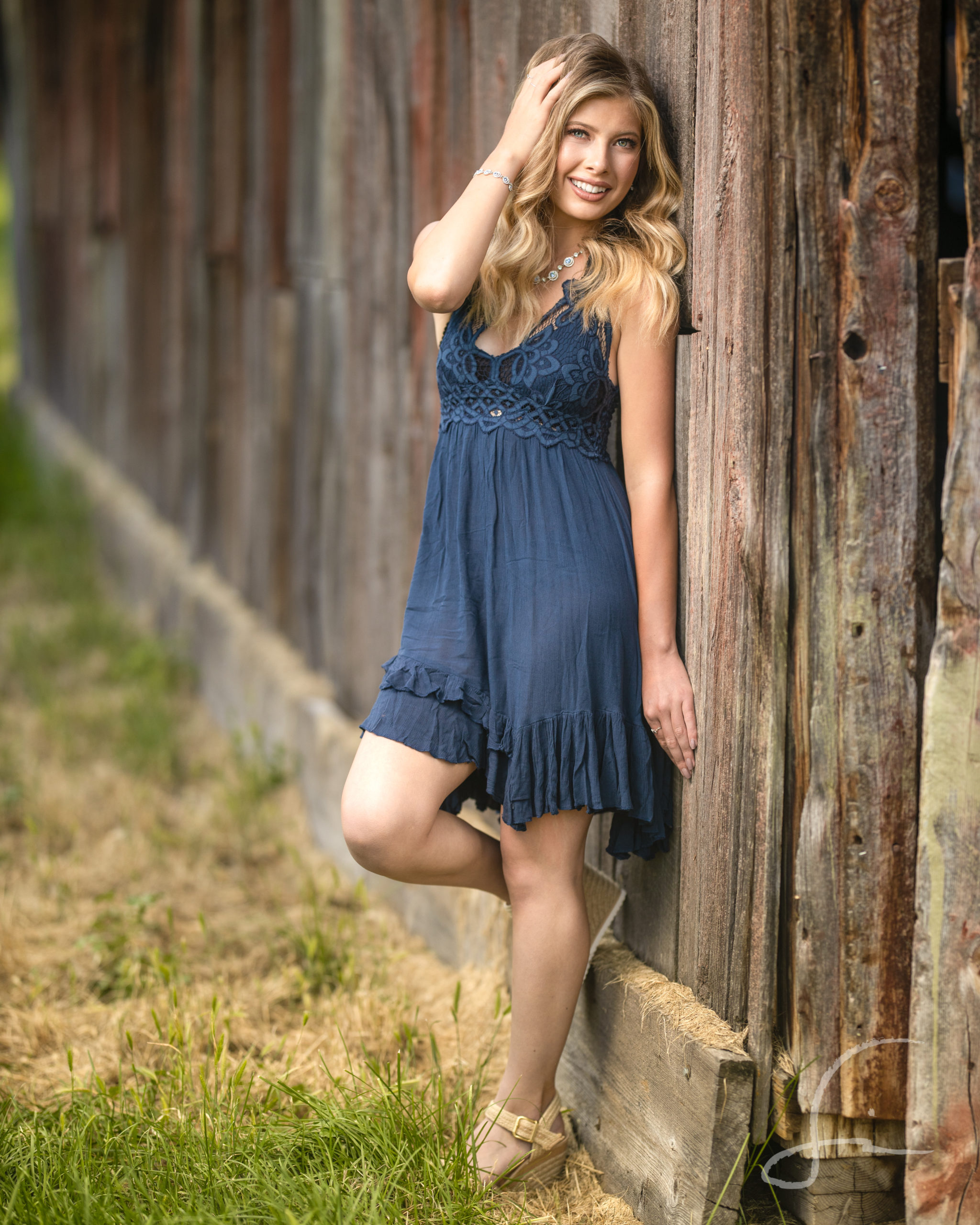 teen girl leaning against a rustic barn in a navy summer dress