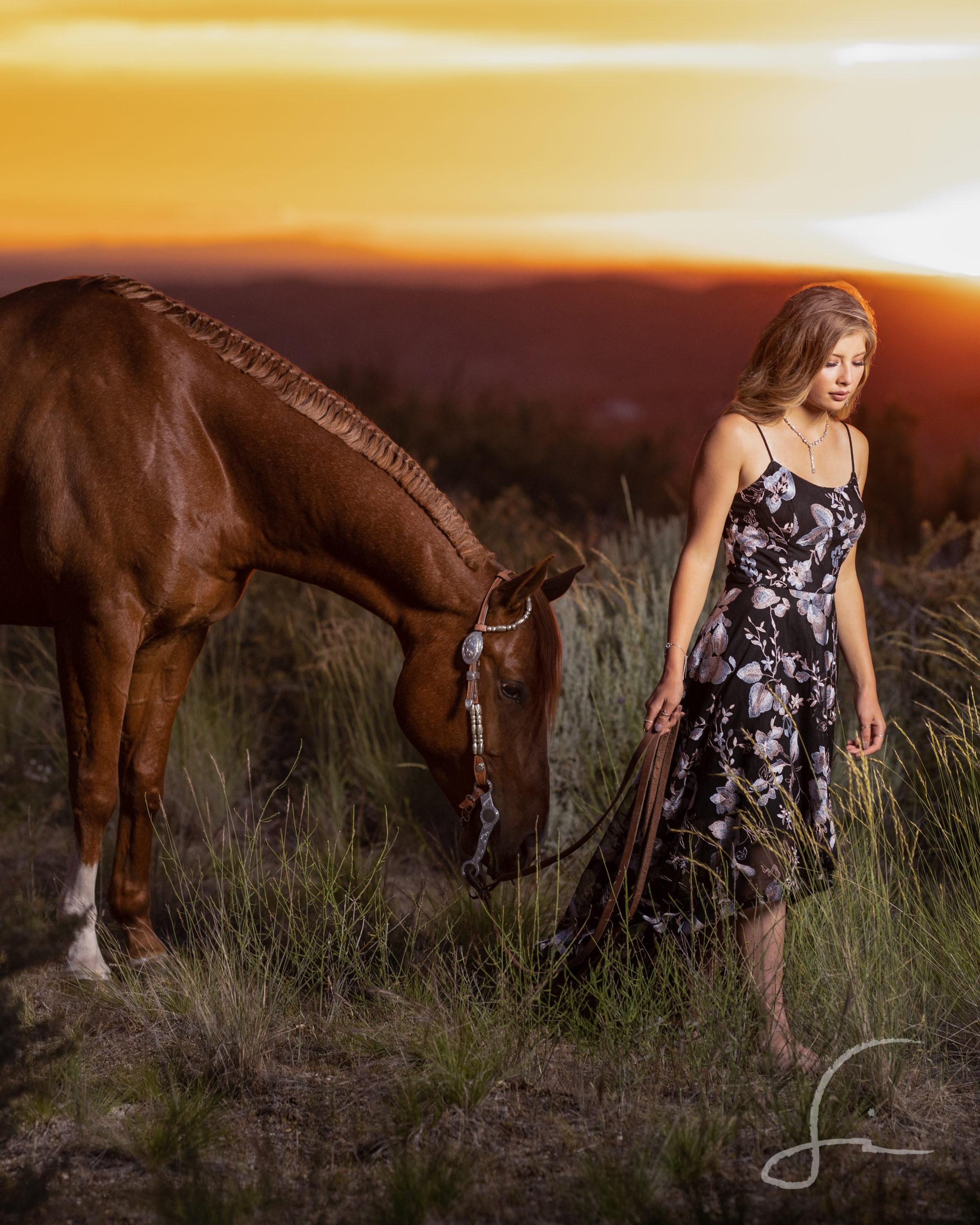 senior high school girl leading her horse at sunset