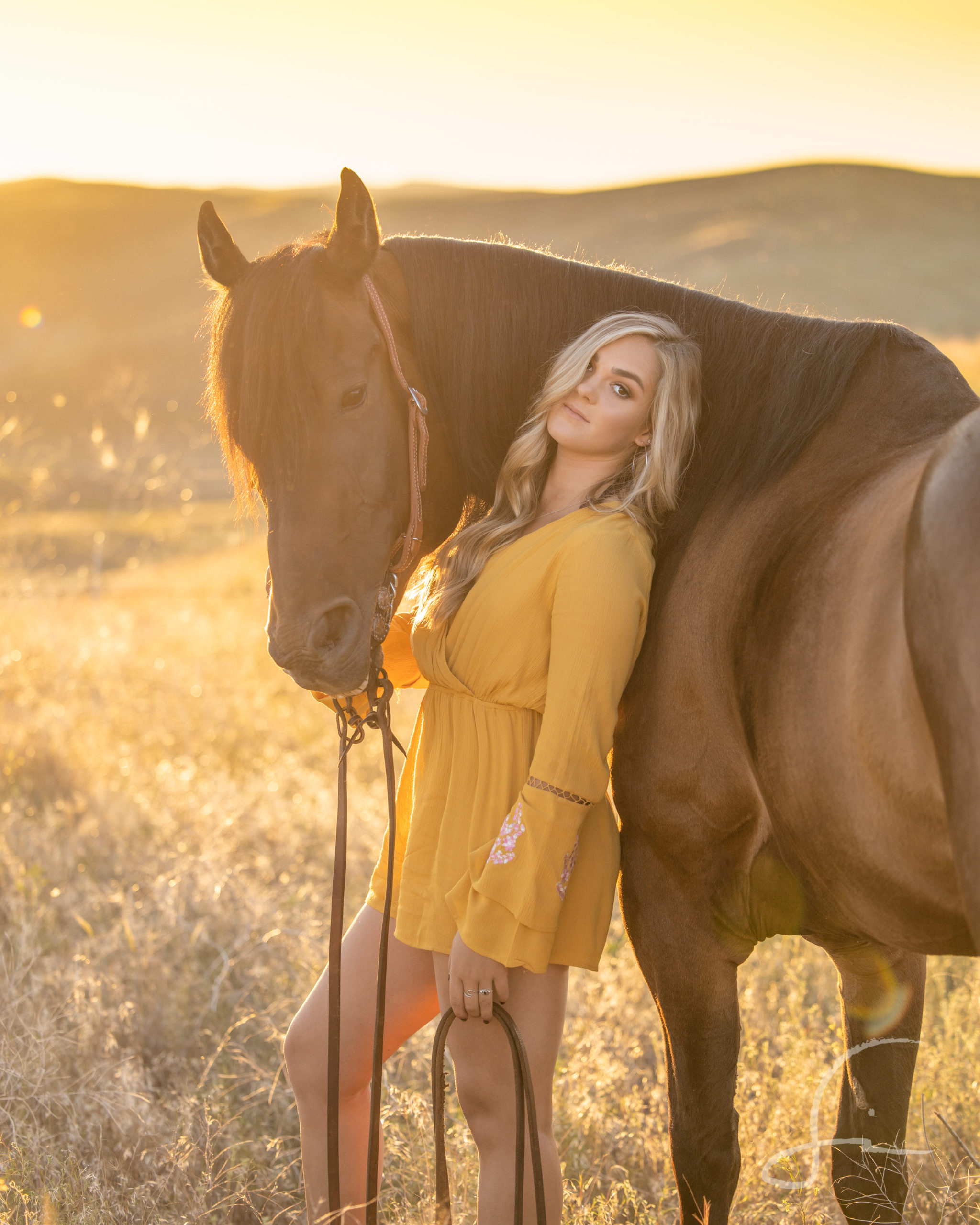 high school senior girl in a mustard romper with her horse in a field at sunset
