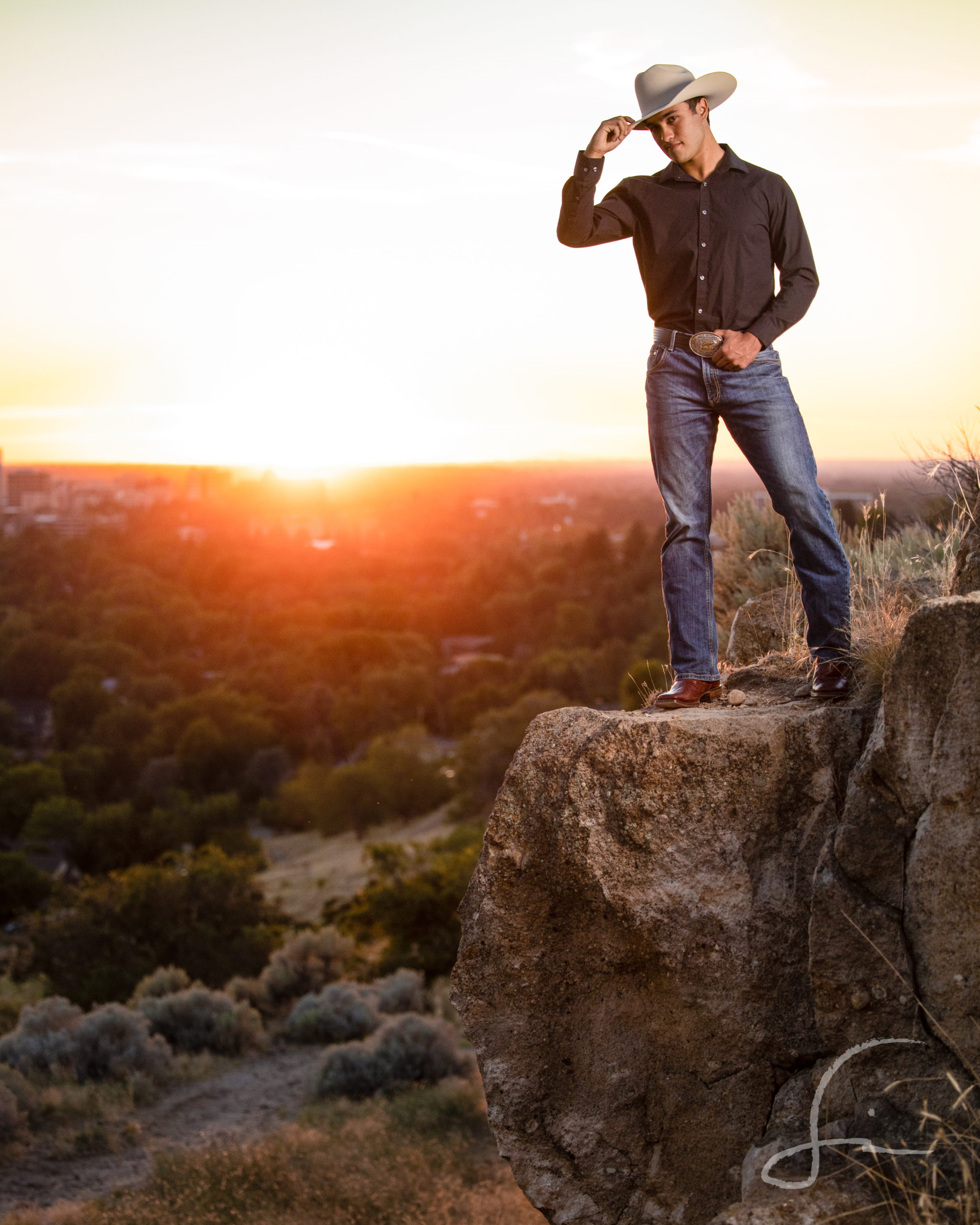 young man on the edge of a cliff over looking the city at sunset in a cowboy hat