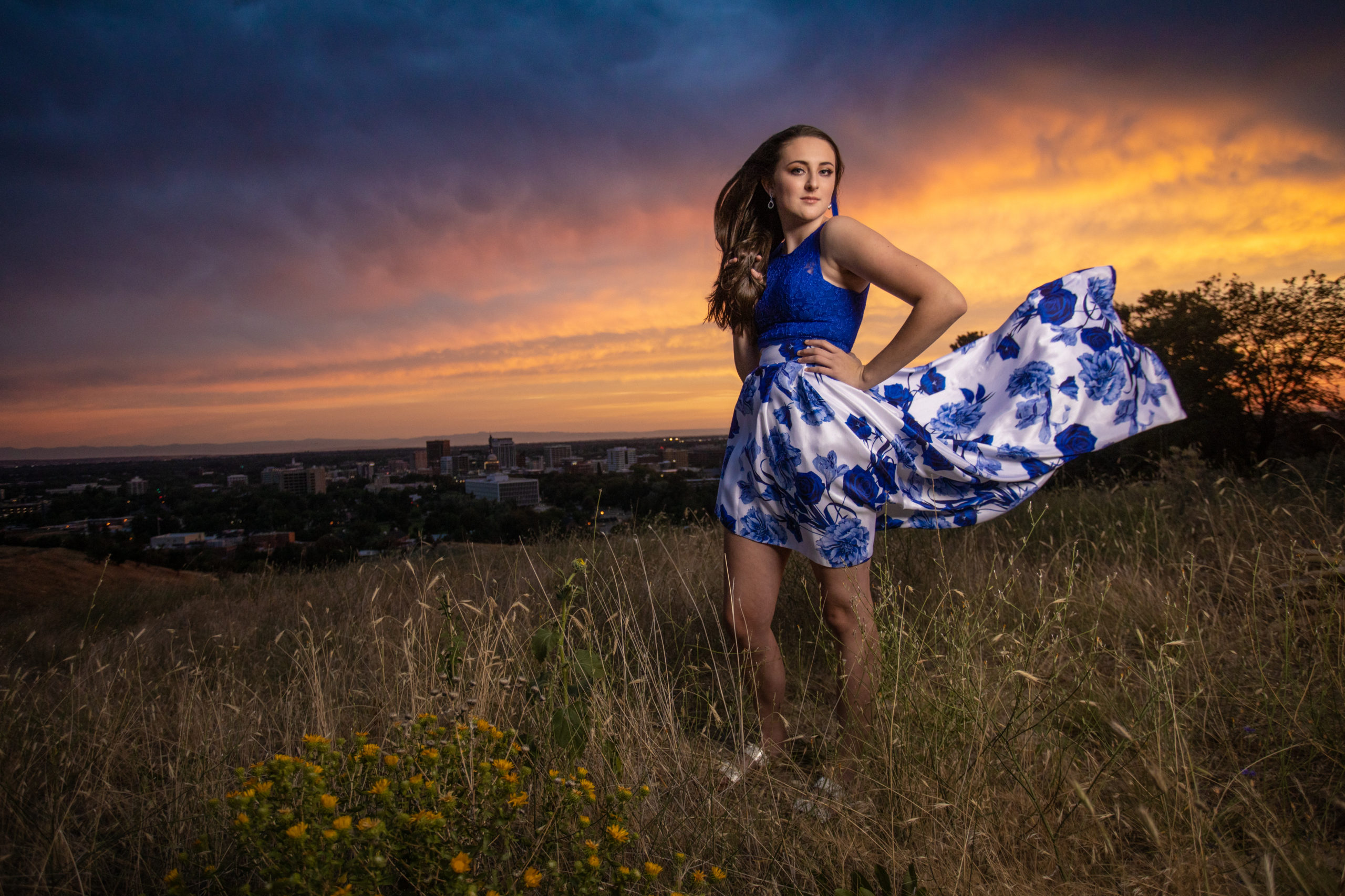 senior girl on hill overlooking the city of Boise Id at sunset