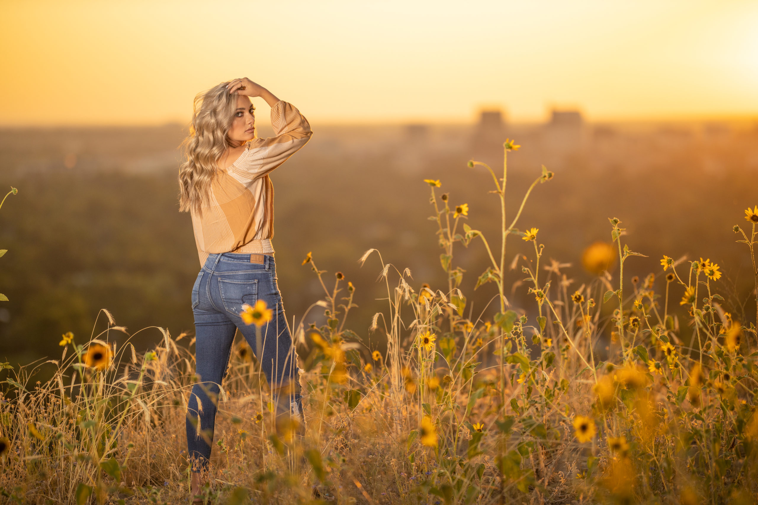 high school senior girl in a field of sunflowers at sunset over looking the city of Boise, Id