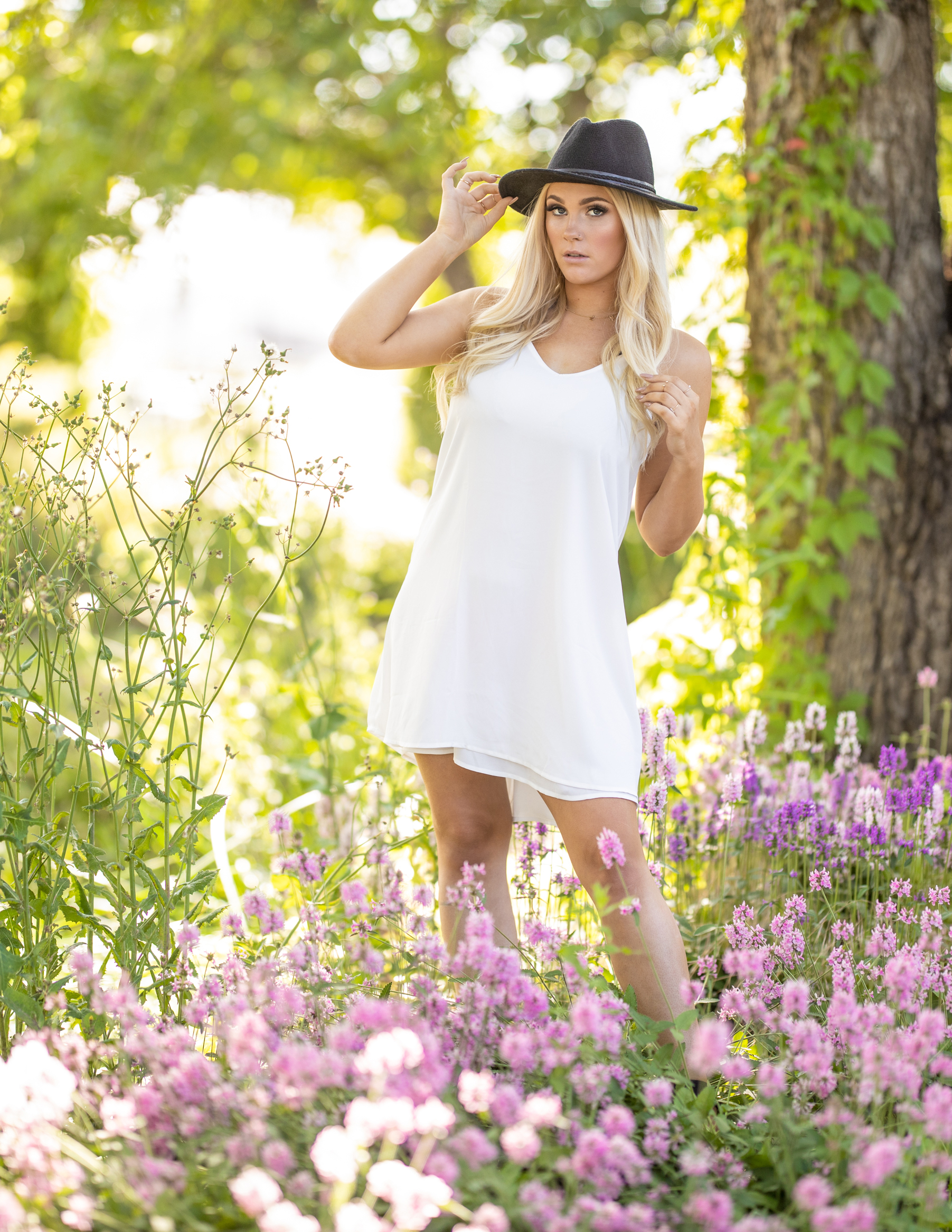 high school senior girl in a white dress in a field of flowers
