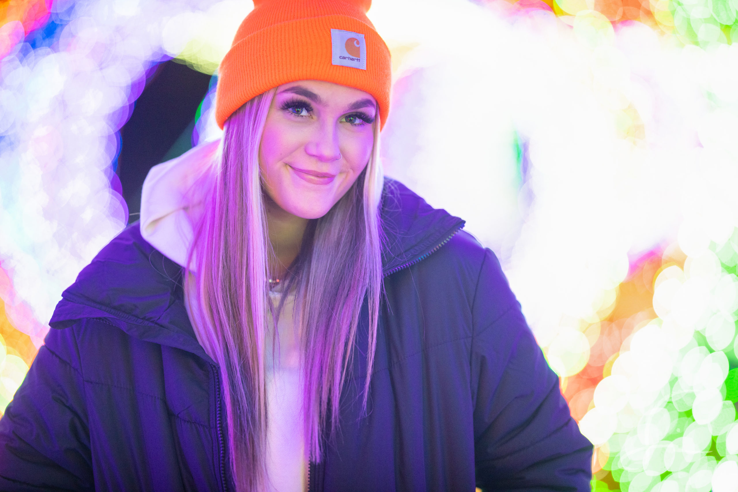senior girl portrait in twinkle lights wearing a jacket and beanie hat