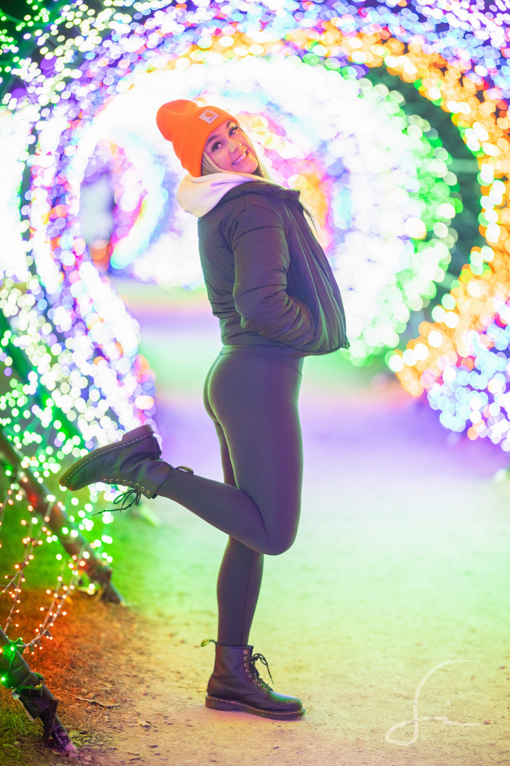 High School Senior Girl in a tube of Christmas Lights wearing leggings, a jacket, and a beanie hat