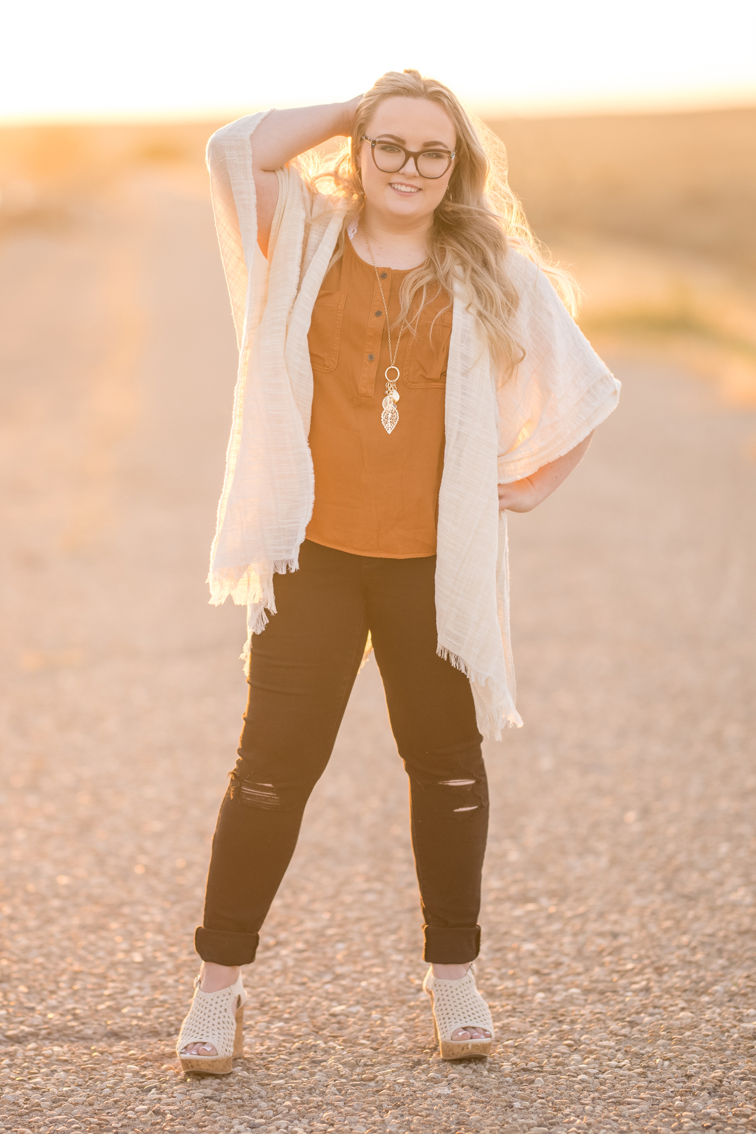 Teen girl in a paved road at sunset wearing black ripped jeans & a cardigan