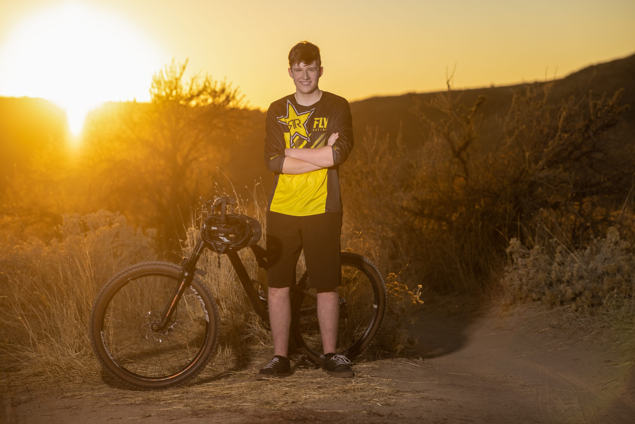 high school senior boy with his mountain bike on a mountain trail at sunset