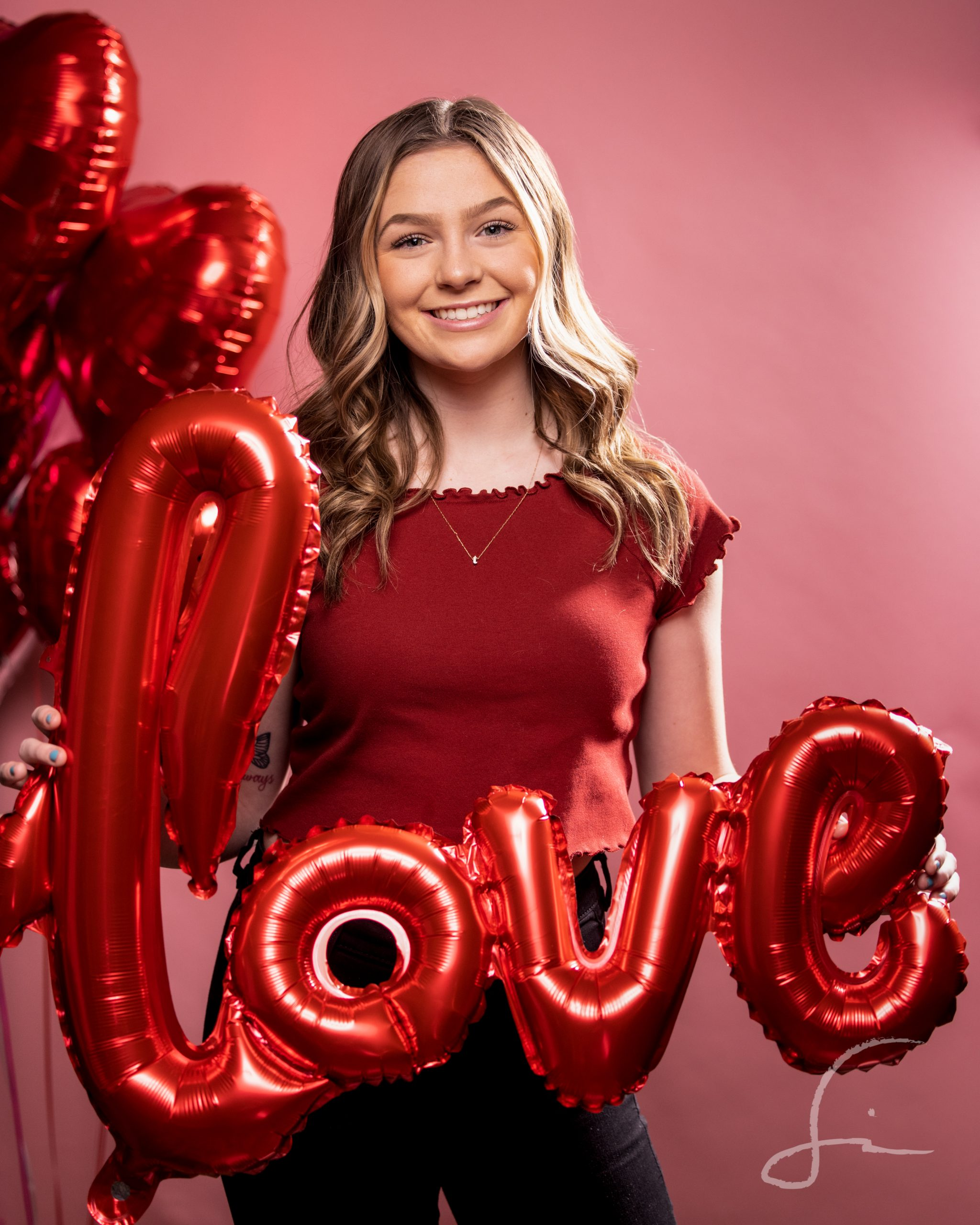Young woman holding a balloon that spells out love on a pink bacground