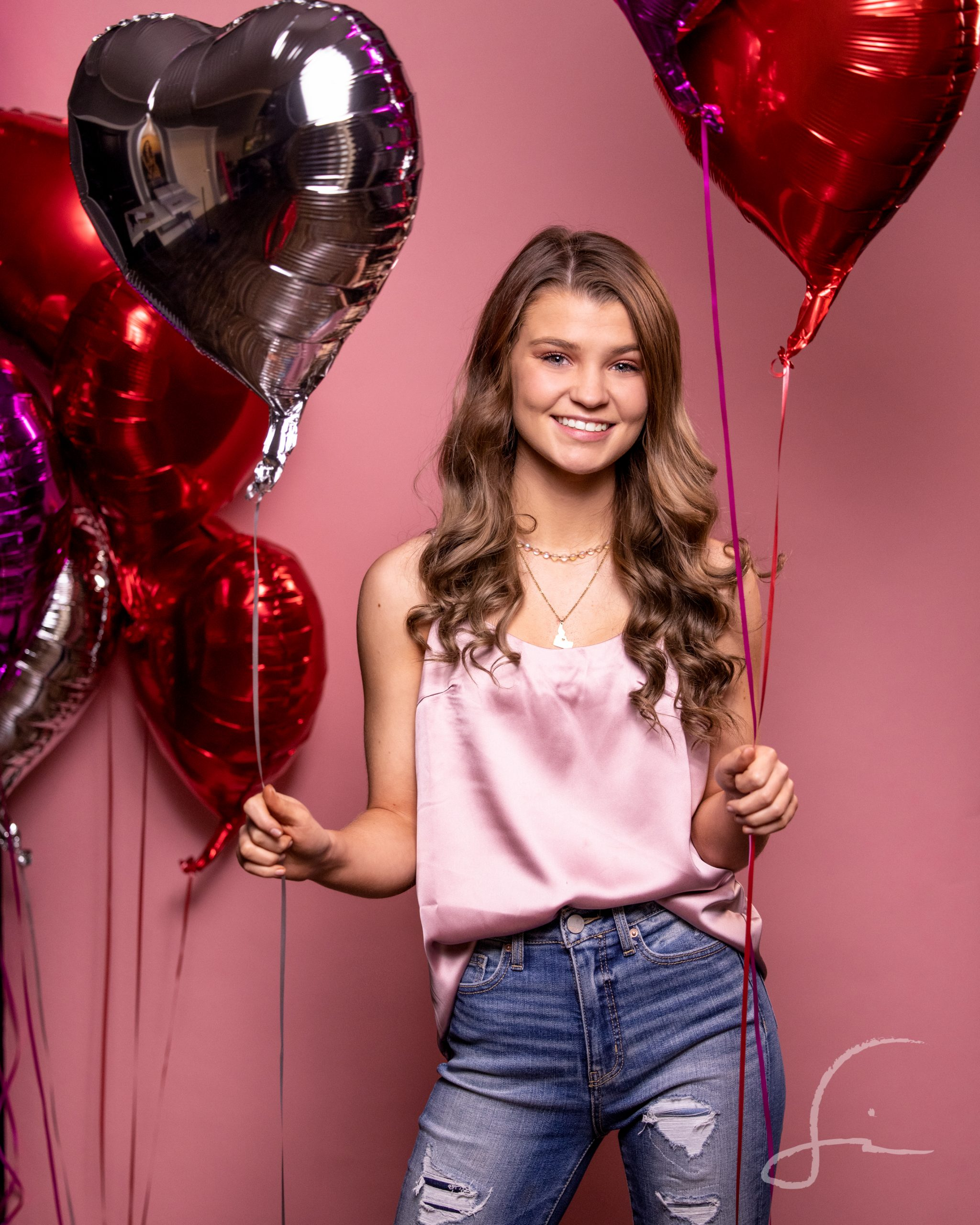 high school senior girl holding heart shaped balloons on a pink backdrop