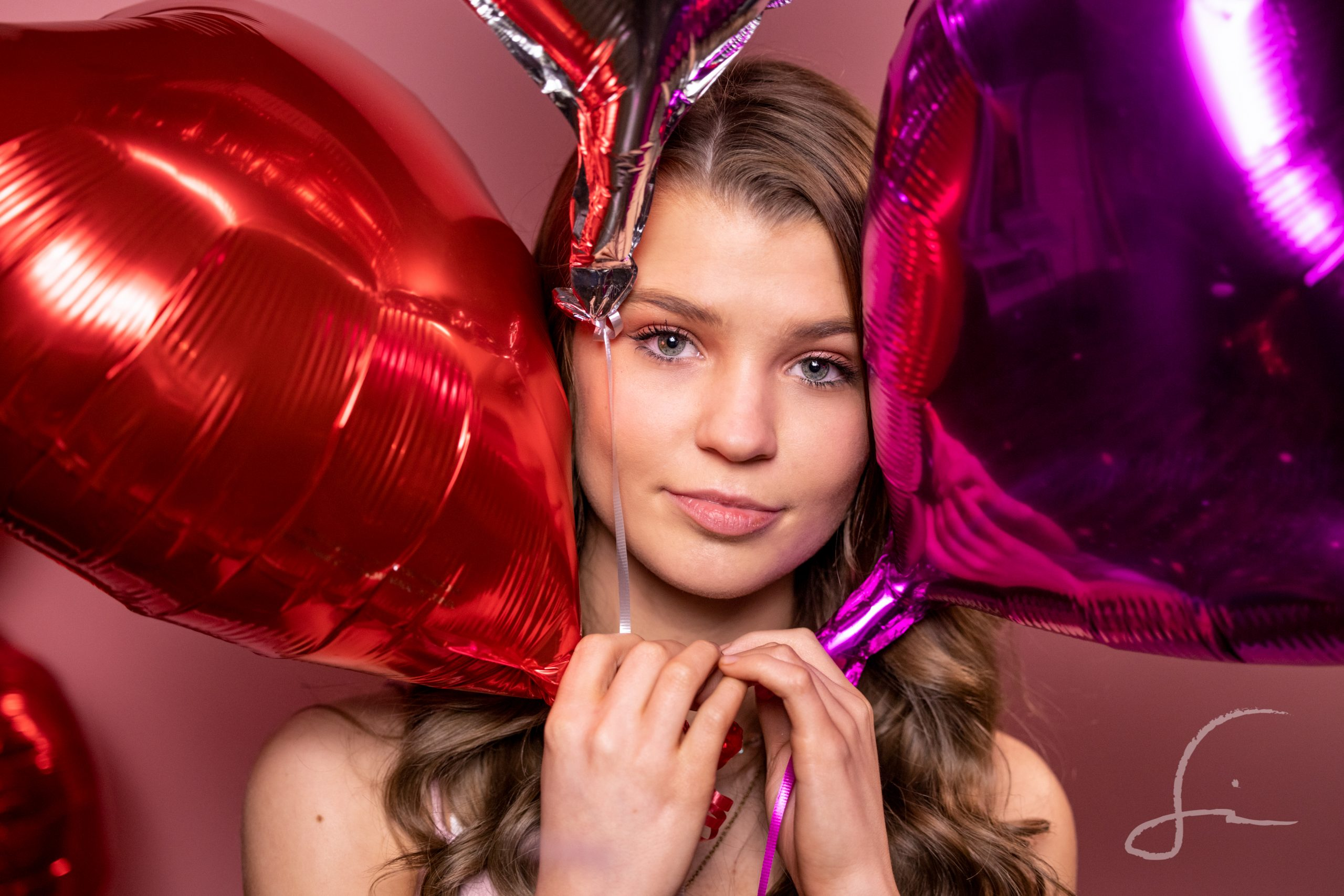 teen girl with pink, purple, and silver, heart balloons