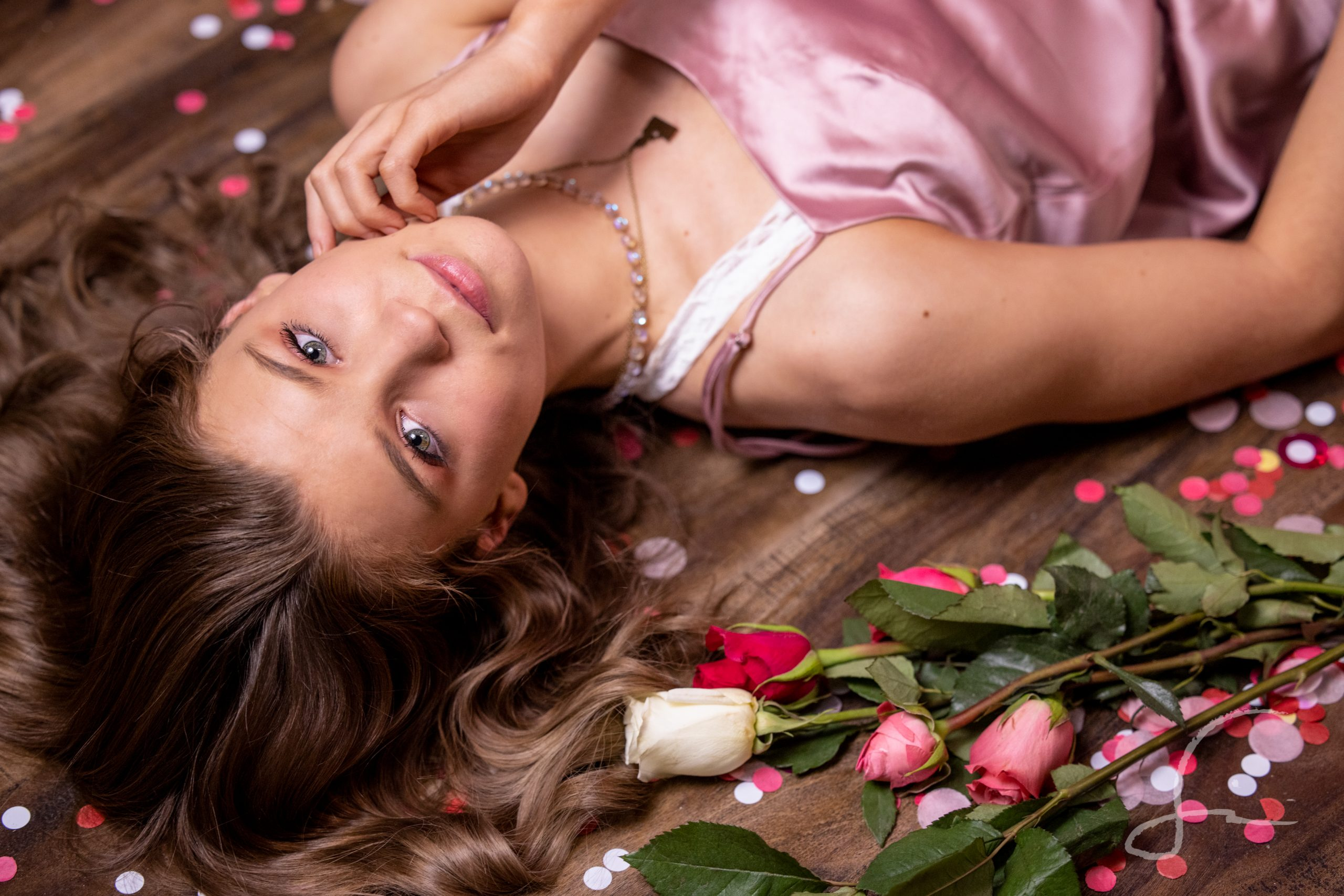 headshot of a young woman amongst roses and pink & white confetti