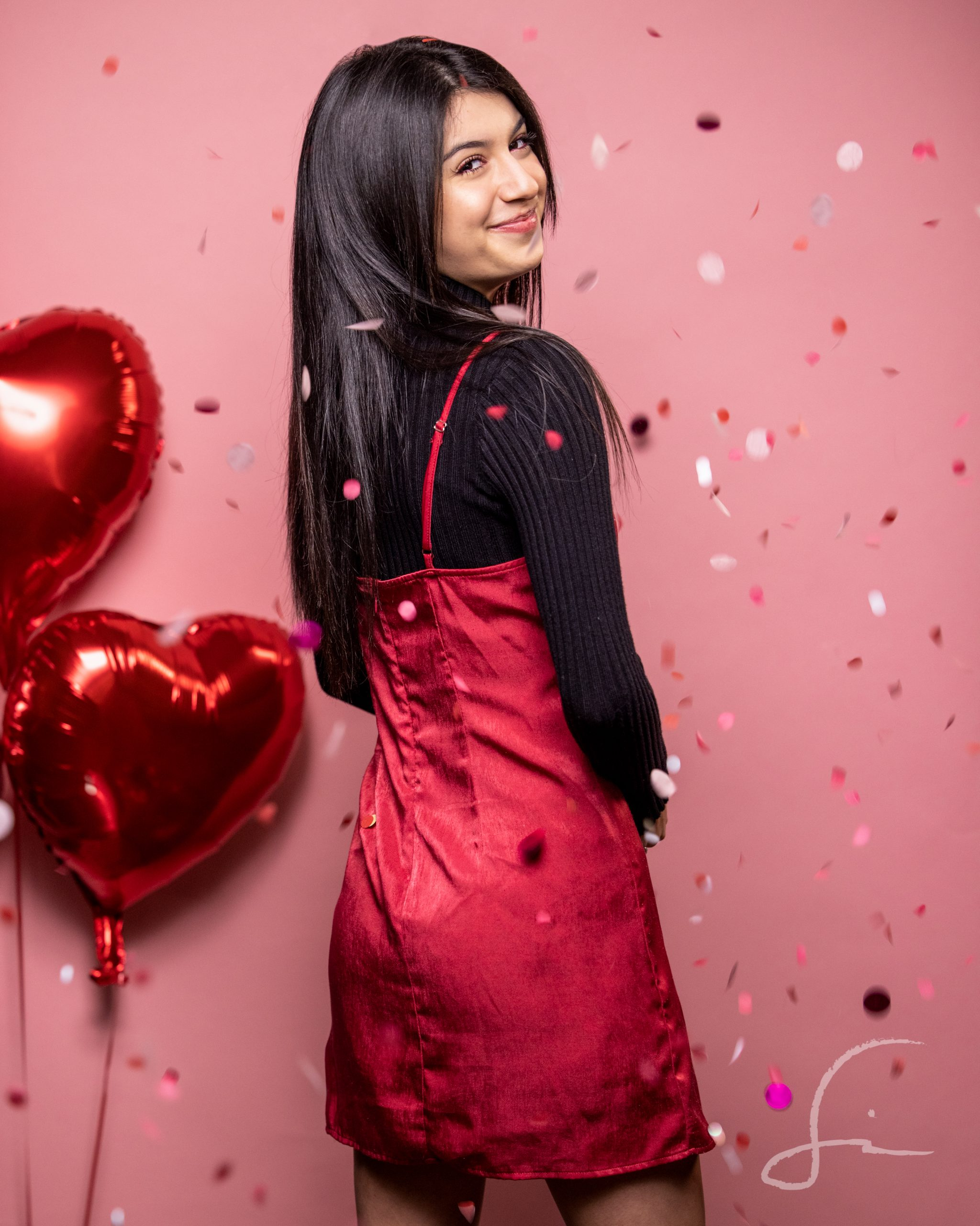 teen girl against a pink background with paper confetti and heart shaped balloons