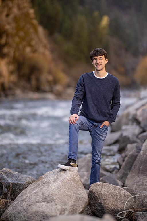 High School senior standing alongside a river for Senior Portraits