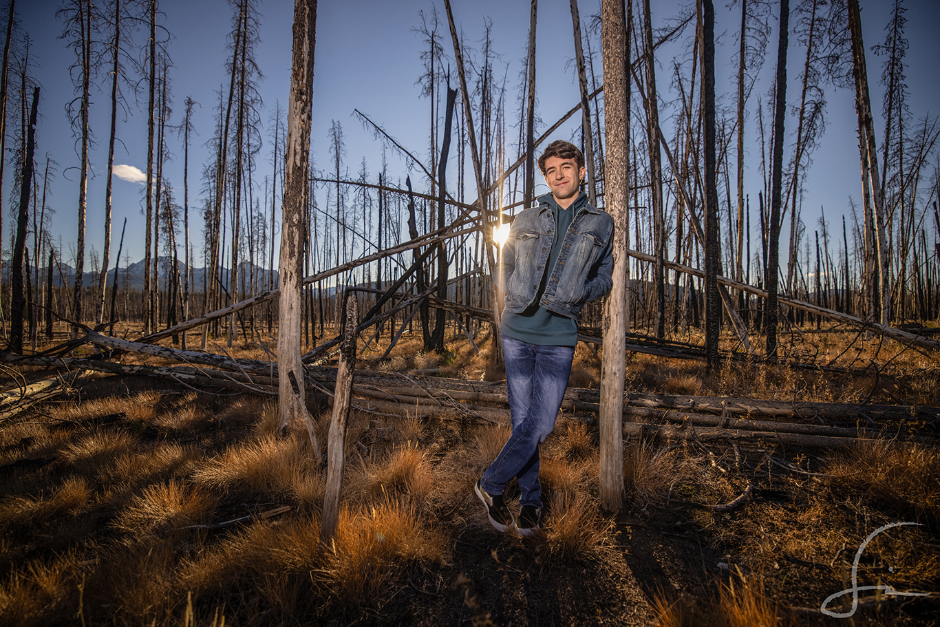 teen boy standing in a burnt out forest for his Senior Portrait