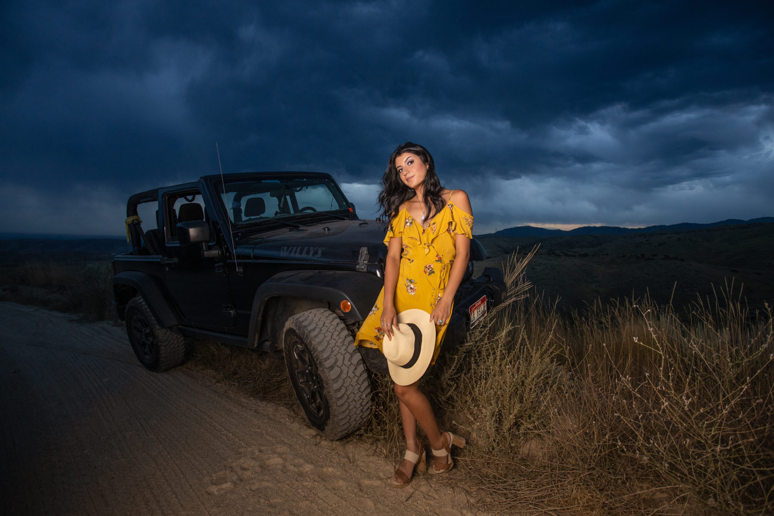 senior high girl at sunset with storm clouds and her jeep