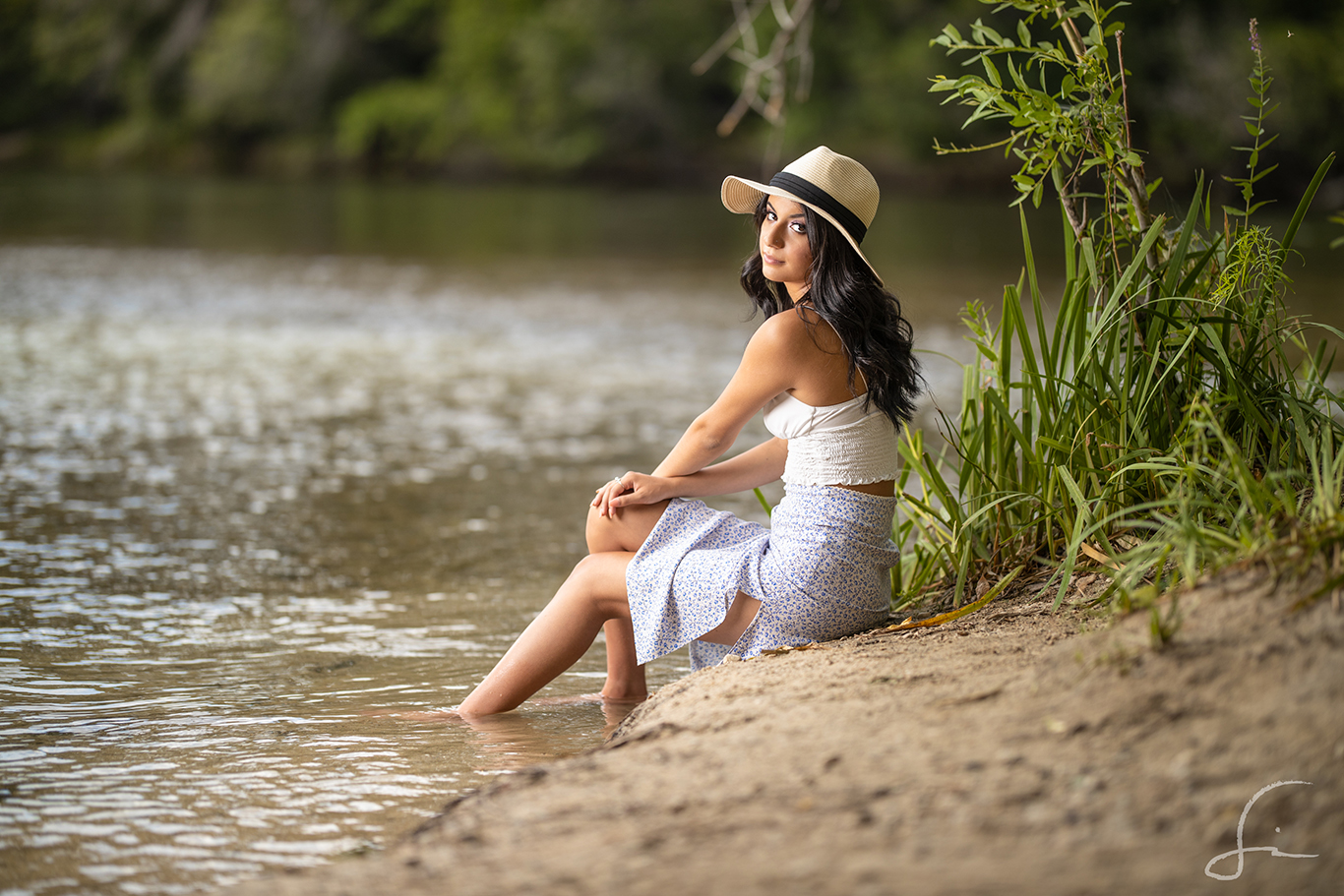 Senior High School girl sitting on the banks of the river with a summer outfit and a bolero hat