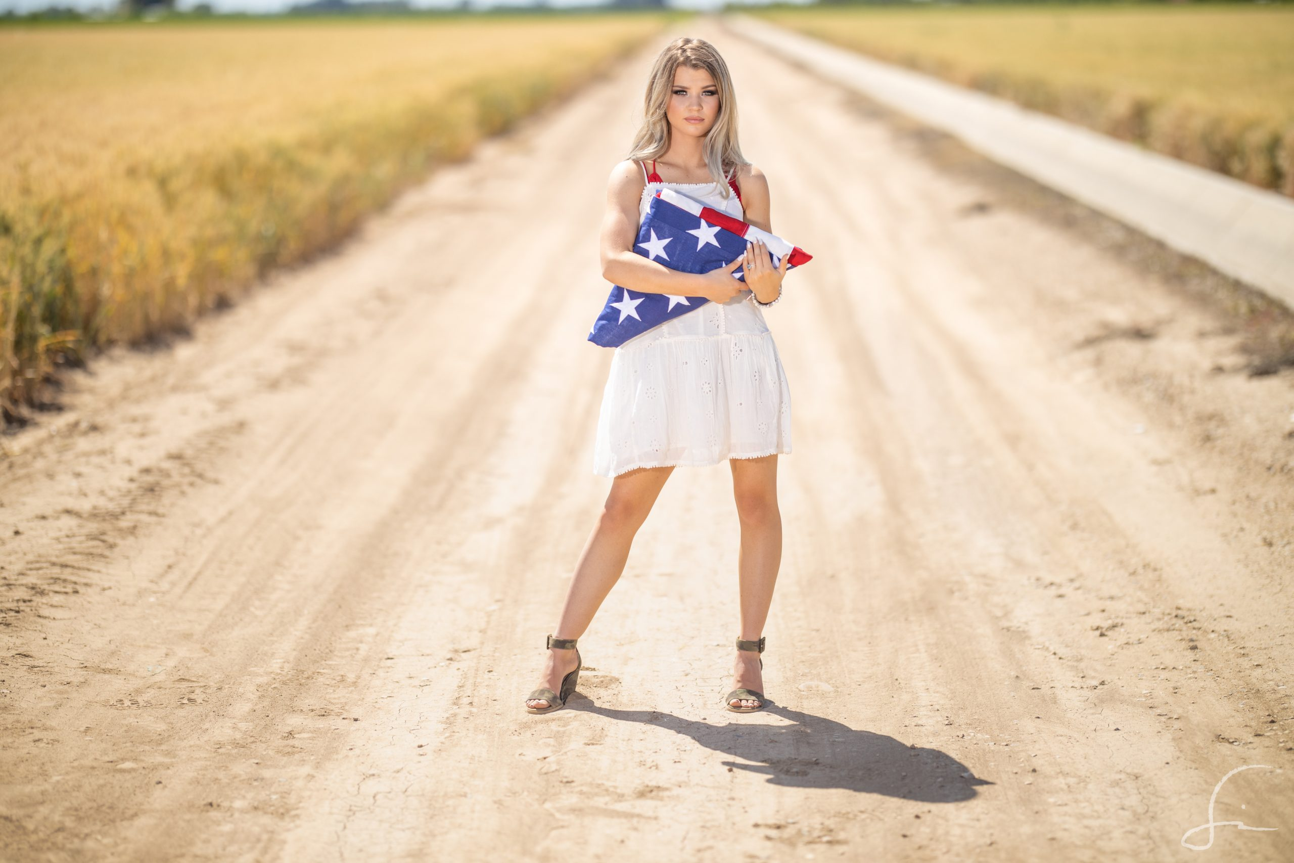 Young woman in a white dress holding an American Flag in a wheat field