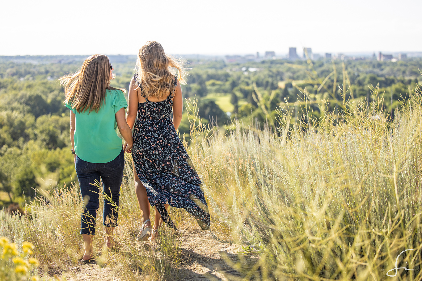 A mother and daughter holding hands, walking away from the camera towards the city