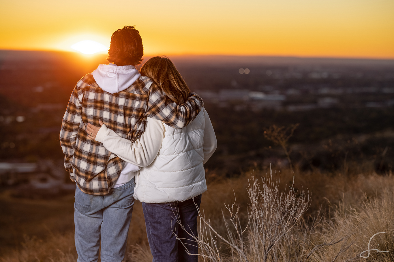 A son holding his mother at sunset in the hills of Boise.