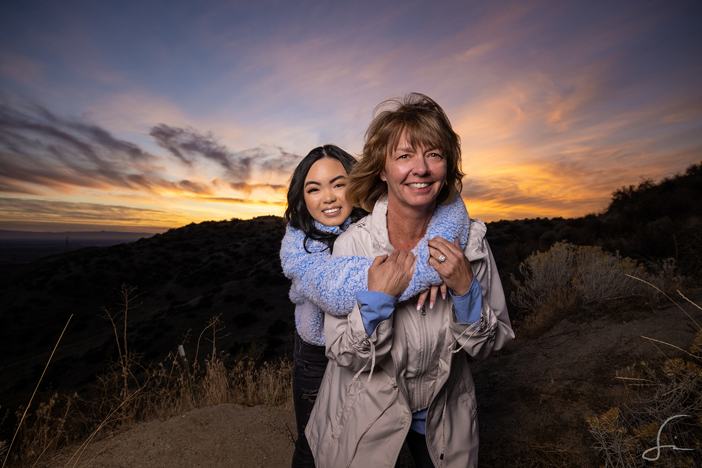 Mother and Daughter standing together for a picture in the hills.