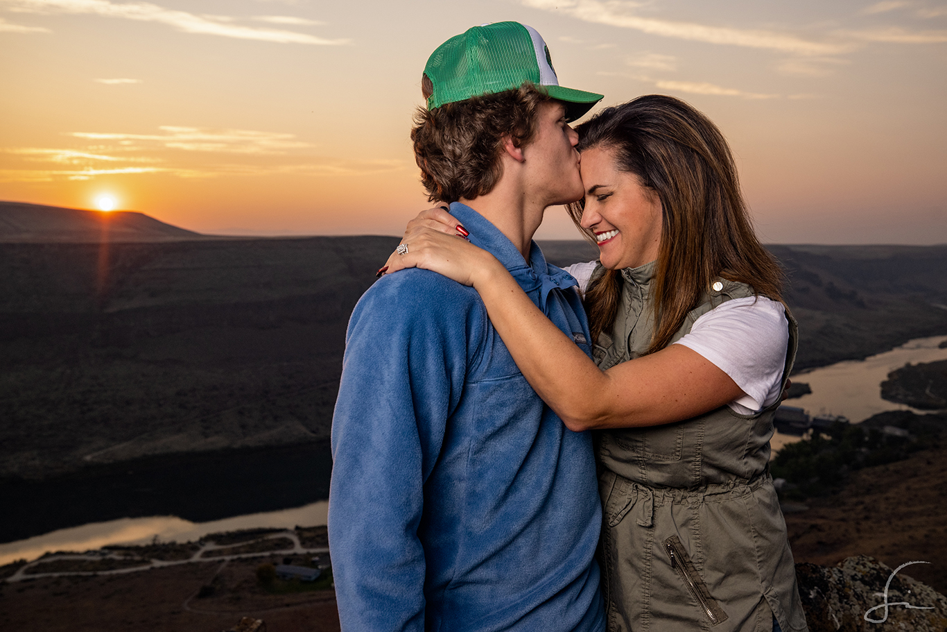 A son kissing his mother on the forehead overlooking the river at Swan Falls Idaho