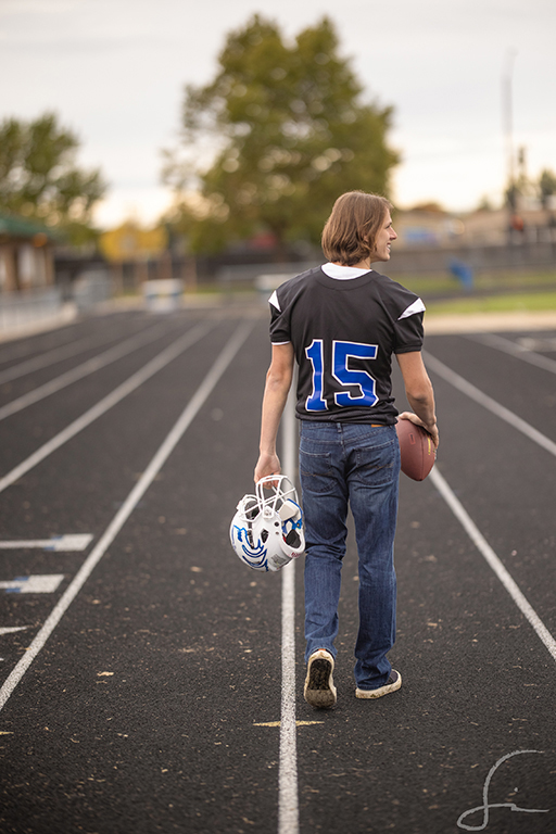 high school senior football player walking on the track of Timberline High school in Boise Idaho holding a football and his helmet