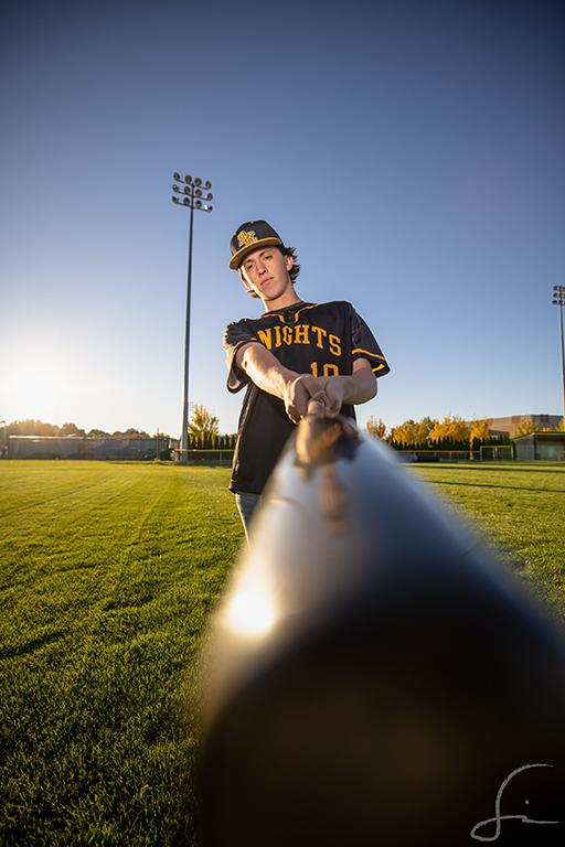 Bishop Kelly baseball player in his senior photos holding his baseball bat towards the camera of Samuel Marvin Photography
