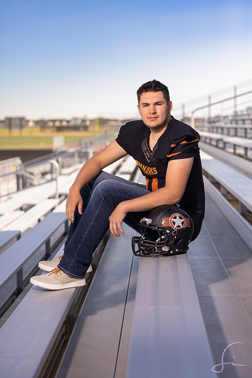 high school senior football player for Ridgevue High in Nampa Idaho sitting on the bleachers of the field for his senior portraits taken by Samuel Marvin Photography